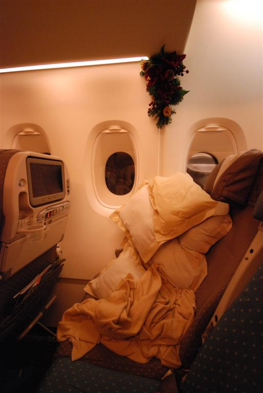 This is my seat. I started off with a single pillow and blanket. There were so few people on the plane that by the time I arrived I had easily 12+ pillows. This is about half way.